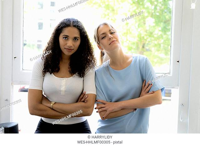 Two female friends sitting at home at the window, looking confident