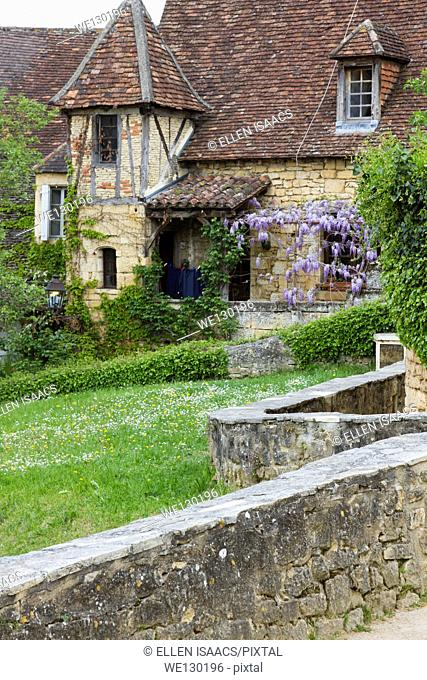 Wisteria growing on charming sandstone cottage with tile roof in Sarlat, Dordogne region of France