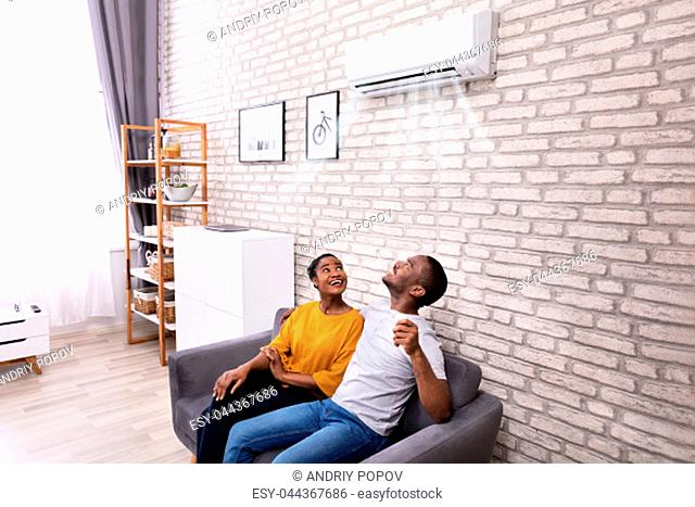Young African Couple Sitting On Sofa Operating Air Conditioner At Home