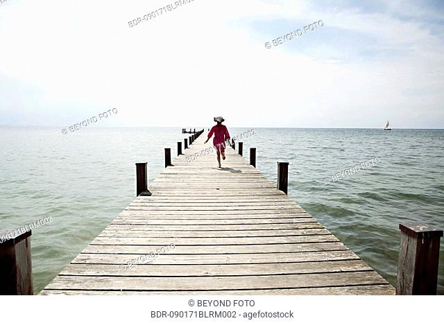 rear view of young girl running on pier