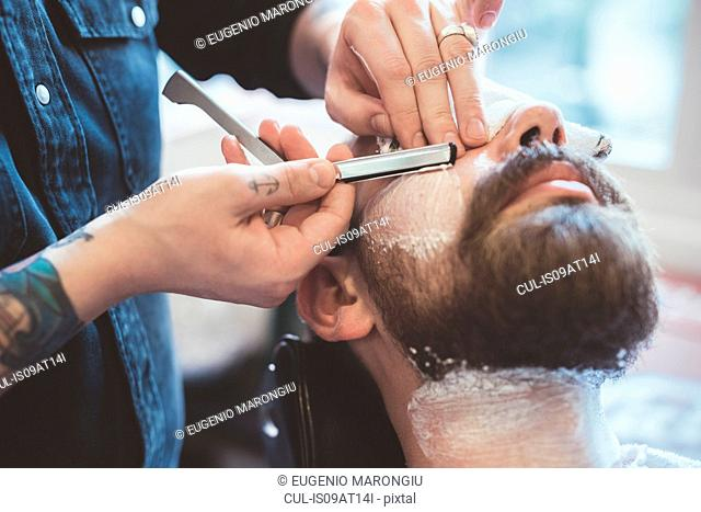 Barber shaving clients face with straight razor in barber shop