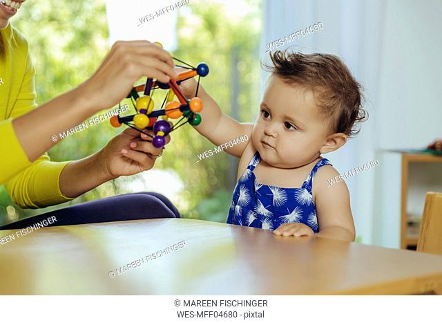 Mother and baby daughter playing at table at home