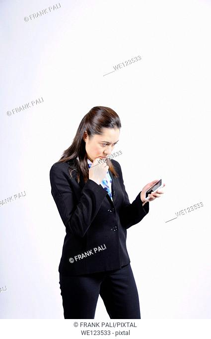 A mixed race woman looking at the telephone  She is wearing a black suit ,she has long brown hair She has her hand under her chin