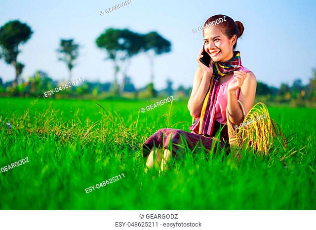farmer woman calling on the mobile phone in a rice field, Thailand