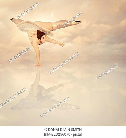 Woman wearing corset and boots balancing on hand in clouds
