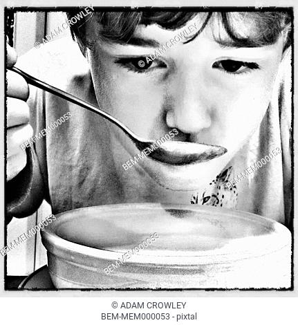 Caucasian boy eating soup
