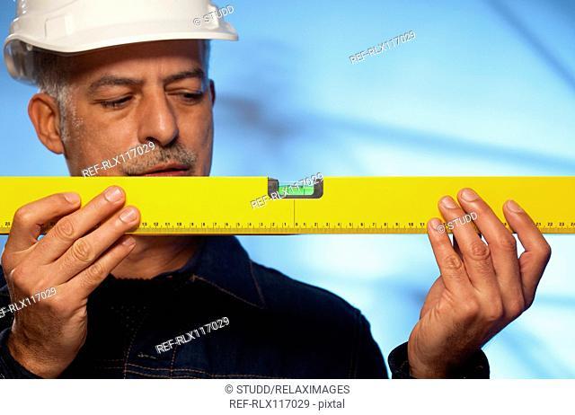 workman holding spirit level construction site old
