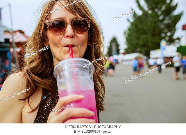 Caucasian woman drinking juice outdoors