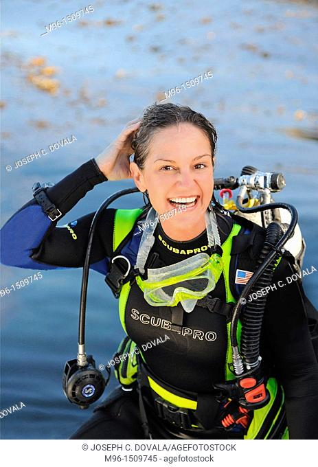 Happy female scuba diver coming up after a dive