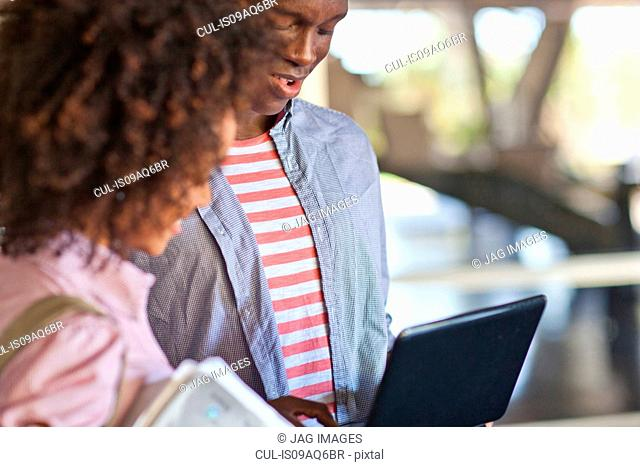 Young couple using tablet, cropped image