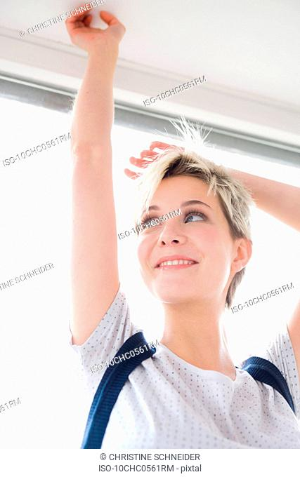 Girl leaning at window arms raised
