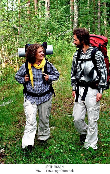 junges Paar wandert froehlich sich unterhaltend in der Natur, MR / young couple hiking cheerful talking in the nature, MR. - 01/01/2005