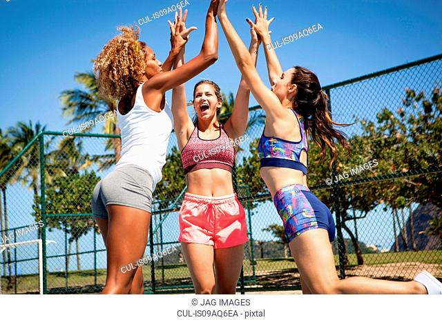 Three women, on outdoor sports court, jumping and giving high fives