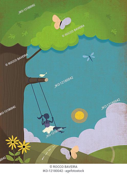 Young girl swinging tree swing in idyllic countryside