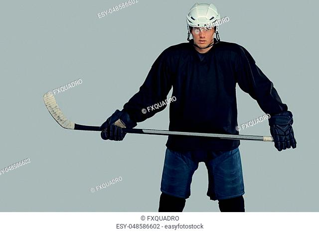 Hockey player wearing black protective gear and white helmet holds a hockey stick. Isolated on a gray background