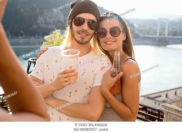Young couple being photographed at roof terrace party, Budapest, Hungary