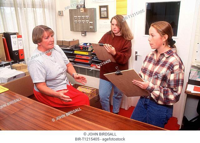 Secondary school pupils holding clipboards interviewing teacher