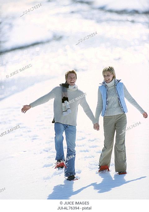 View of a young couple snowshoeing in winter setting