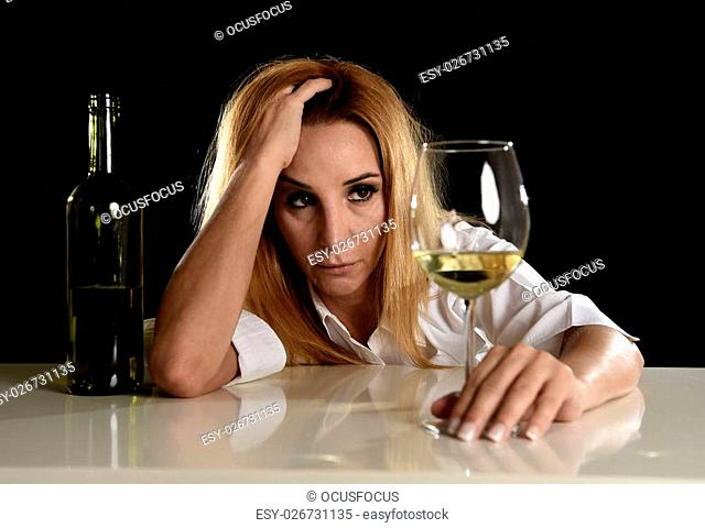 drunk blond woman alone in wasted depressed face expression looking thoughtful holding white wine glass isolated on black background in alcohol abuse and...