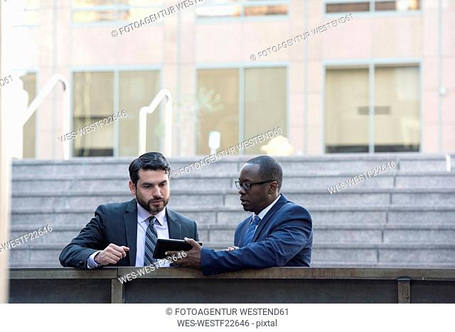 Two businessmen sharing tablet outdoors