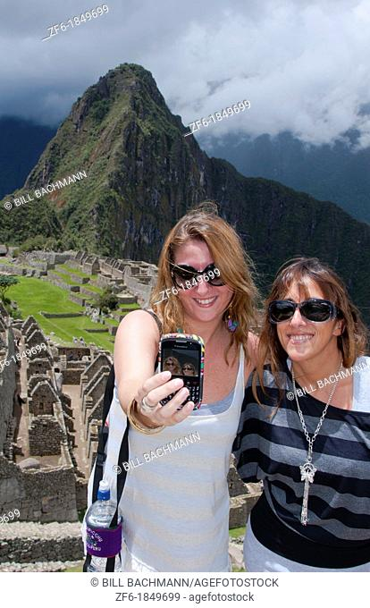 Machu Picchu famous ruins from above with two European tourists taking cell photo in Peru from Inca history