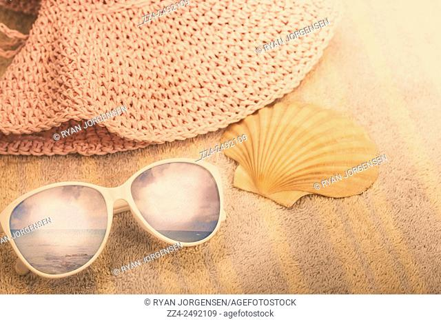Retro filtered still life photograph of womens sun glasses sitting on a striped beach towel with hat and shell. Australian summer holidays