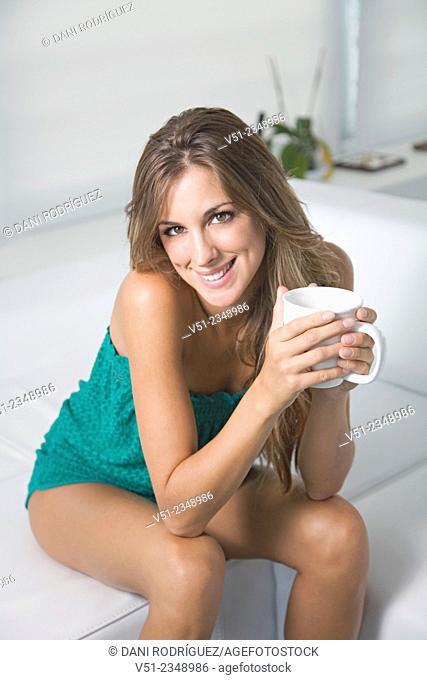 Portrait of a blonde woman at home with a cup of coffee smiling at camera in the living room