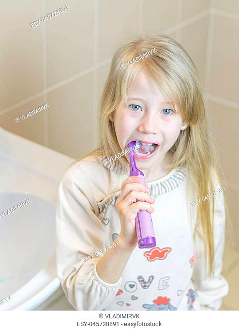 Girl brushing her teeth electric toothbrush with your mouth open. The concept of oral care