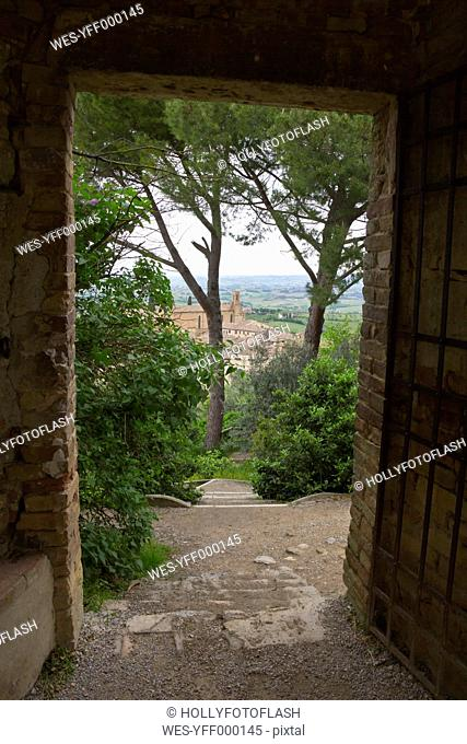 Italy, Tuscany, San Gimignano, View through open paled gate to city