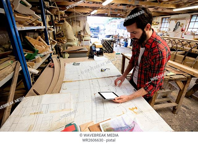 Man using digital tablet while looking at blueprint