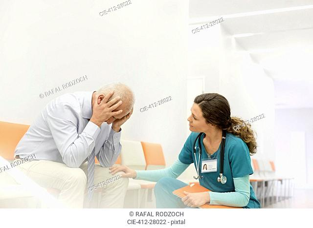 Nurse consoling upset man in clinic corridor