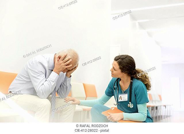 Nurse consoling upset man in clinic corridor