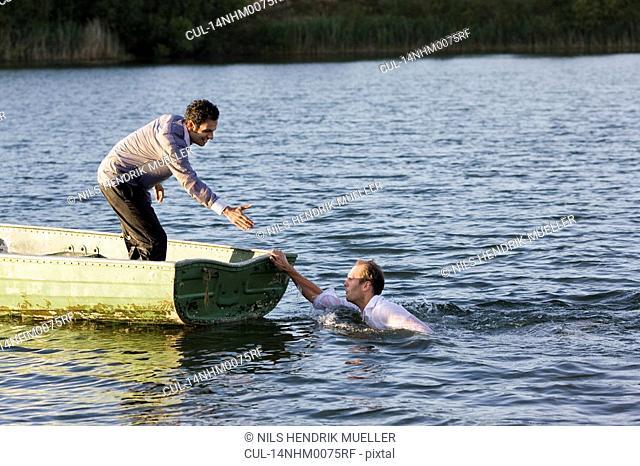 businessman helping man overboard