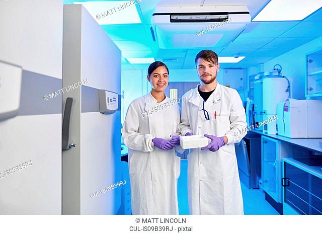 Scientists in laboratory looking at camera