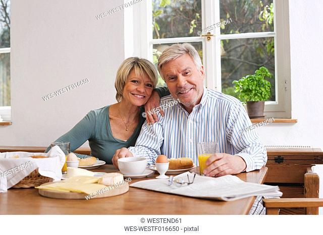 Germany, Kratzeburg, Senior couple having breakfast, smiling, portrait