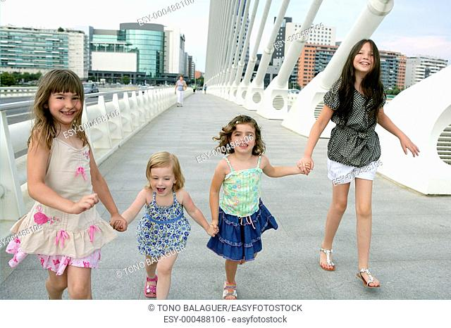 Four little girl group walking in the city bridge downtown buildings