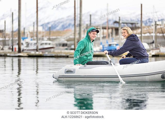 Young adults paddling a skiff in Homer, Kenai Peninsula, Southcentral Alaska