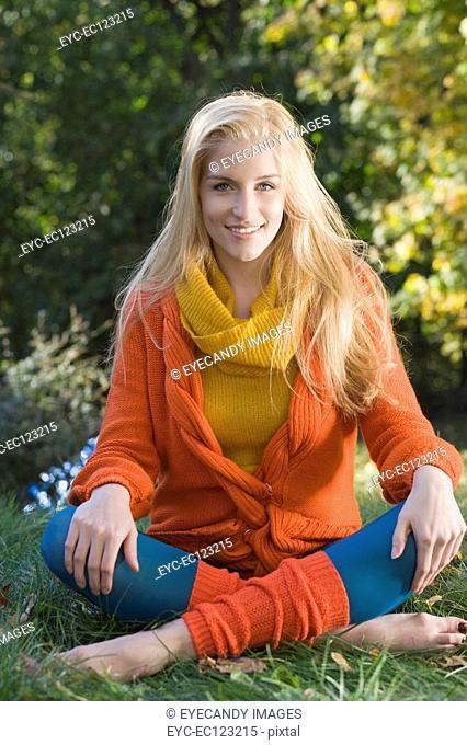 Portrait of stylish young woman sitting on grass barefoot