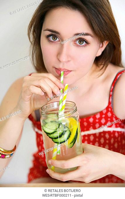 Portrait of woman drinking detox water infused with lemon and cucumber
