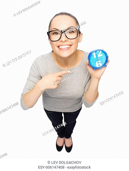 time and deadline concept - smiling woman in eyeglasses pointing to blue clock