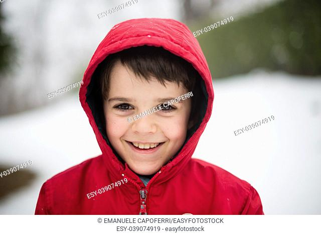 portrait of smiling child with red hat in snowy forest