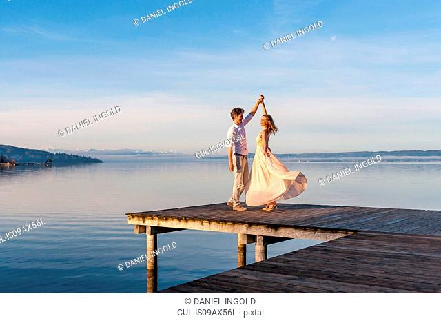 Couple with arms raised dancing on wooden pier in ocean