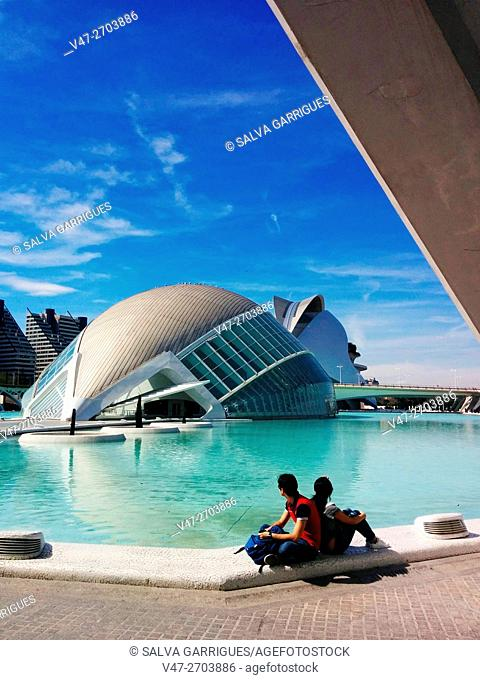 Couple of tourists sitting on the lake and watching the Hemisferic, Valencia, Spain. Europe