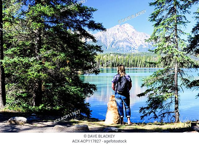 A woman and her Golden Retriever pause while hiking around Lac Beauvert in Jasper National Park in Jasper, Alberta. Pyramid Mountain is in the background
