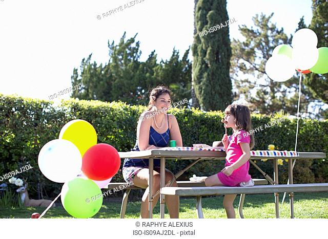 Mother and daughter sitting at party table in garden