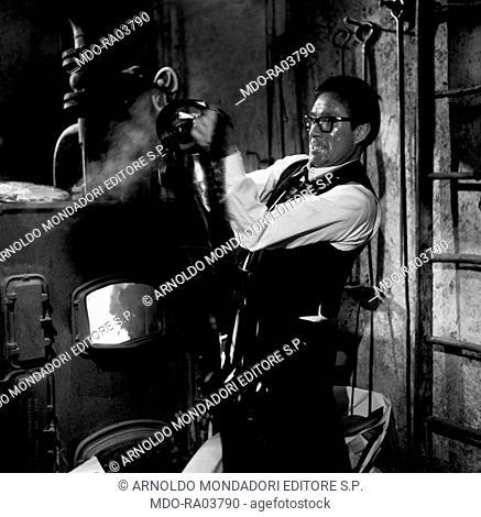 Italian actor Ugo Tognazzi holding a film beside the furnace in the film Complexes, segment Il complesso della schiava nubiana. 1965