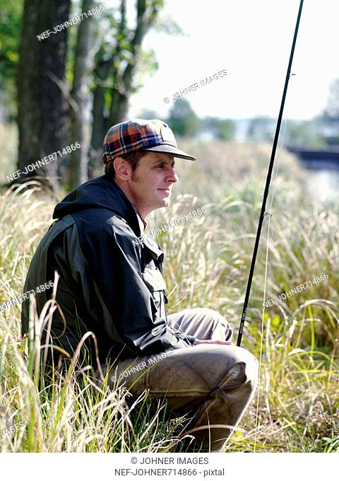 Angler sitting in the reed, Sweden