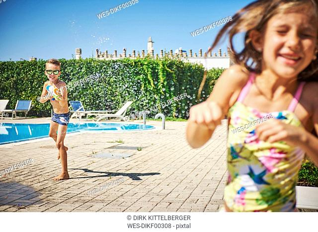 Boy with water gun splashing at girl at the poolside