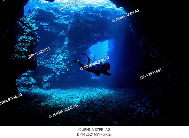 Scuba diver swims through lava arches with sun rays, Cathedrals dive site; Lanai City, Lanai, Hawaii, United States of America