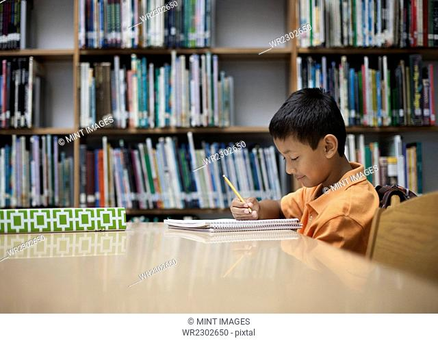 A boy sitting at table in a school library, using a pencil, studying